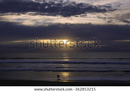 solo surfer at sunset - stock photo