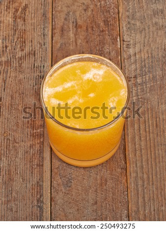 Soluble vitamin orange in a glass on a wooden background - stock photo