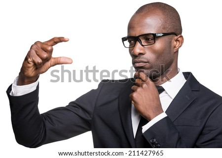 Solution in his hand. Thoughtful young African man in formalwear holding small copy space and looking at it while standing isolated on white background  - stock photo