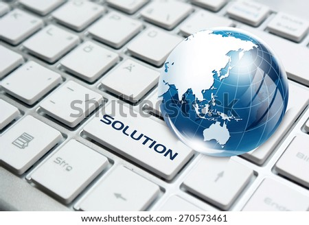 Solution key and glass globe over white computer keyboard - stock photo