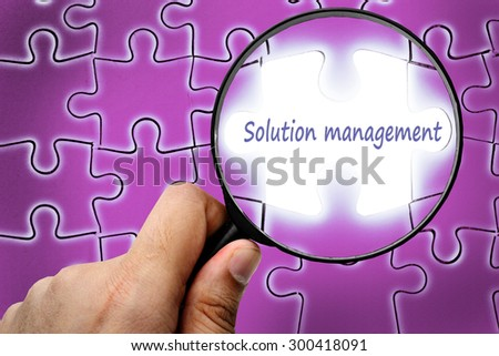 Solution management word. Magnifier and puzzles. - stock photo