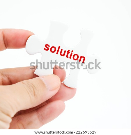 Solution word on white puzzle piece in hand isolated on white background, solution concept, business background