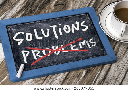solutions and problems concept handwritten on blackboard - stock photo