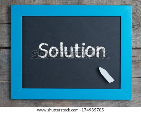 Solutions title word written on blue framed chalkboard on wooden background  - stock photo