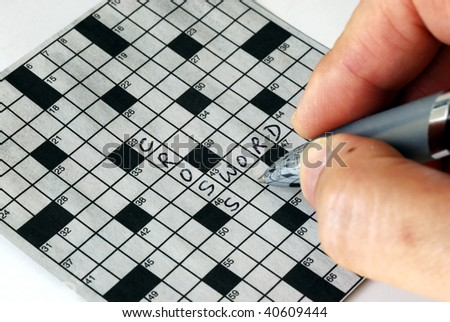Solving the cross word puzzle from the newspaper - stock photo