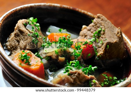 Solyanka soup with various sorts of meat, potatoes, olives, carrot, onion.