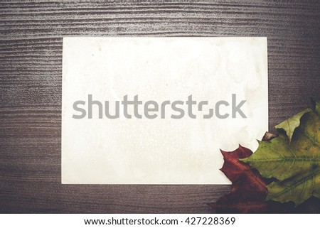 some autumn leaves and blanck old photo on wooden table - stock photo