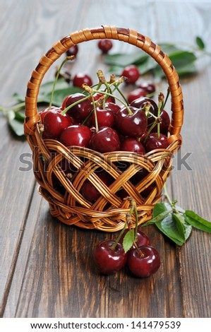 Some beautiful sweet cherry in a basket on wooden background
