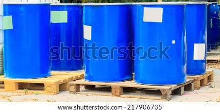 Some blue barrels standing on wooden pallets on a chemical plant - stock photo