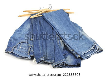 some blue jeans in wooden clothes hangers on a white background - stock photo