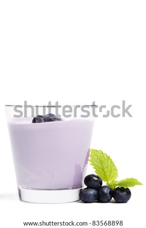 some blueberries with melissa near a milkshake with blueberries on white background - stock photo
