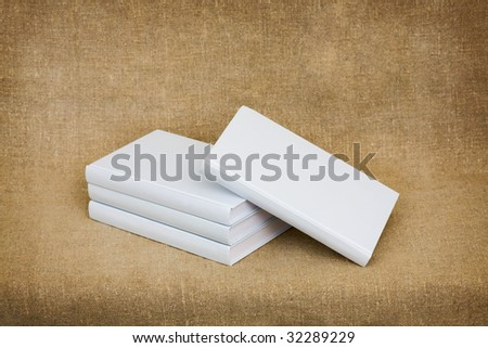 Some books with light covers against a sacking - stock photo