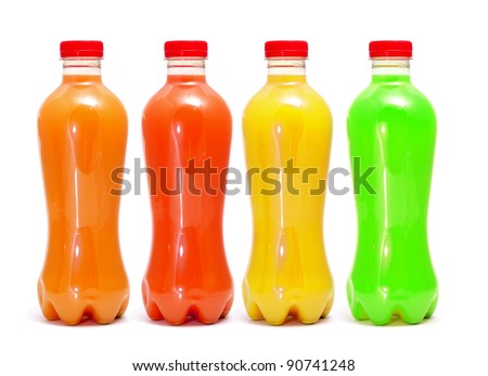 some bottles of different colors with different juices on a white background - stock photo
