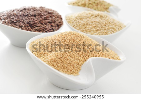 some bowls with amaranth, brown flax, quinoa and buckwheat seeds on a white surface - stock photo