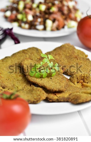 some breaded fillets of seitan in a white ceramic plate, placed on a white table with a lentil salad in the background - stock photo