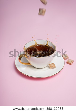 some brown sugar cubes dropping into white  coffee cup on pink background - stock photo