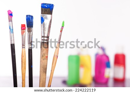 Some brushes with colores in front of colored pallet. Isolated on white. - stock photo