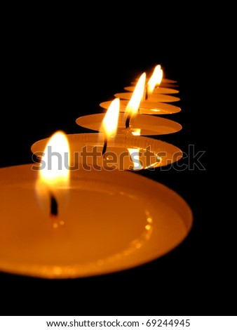 Some burning candles on a black background. - stock photo