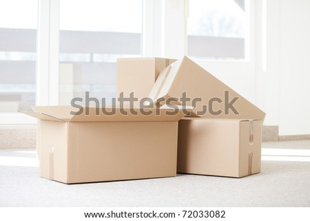 some cardboard boxes in an empty room with space for ypur own text - stock photo