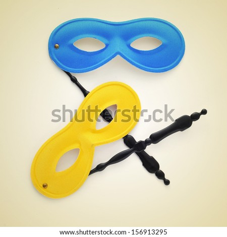 some carnival masks on a beige background, with a retro effect - stock photo
