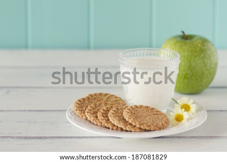 Some cereals cookies, a milk glass and a apple on a white wooden table with a robin egg blue background. Vintage - stock photo