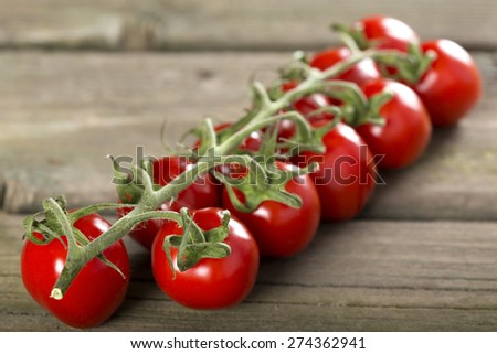 Some cherry tomatoes on a wooden surface - stock photo