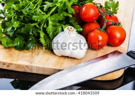 some cherry tomatoes, parsley and garlic on a cutting board isolated over a dark surface