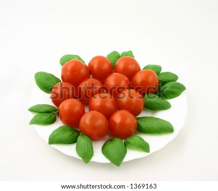 Some cherry tomatoes put together with fresh basil leaves (this is the version without dewdrops) - stock photo