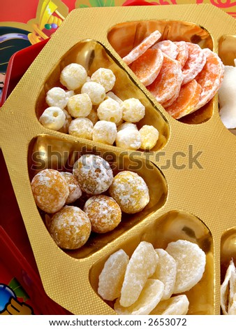 Some Chinese New Year candies on a gold and red background - stock photo