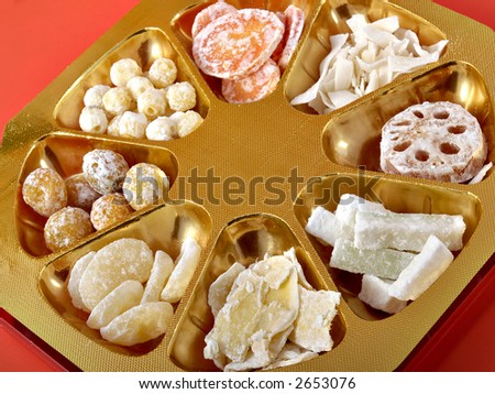 Some Chinese New Year candy on a red and gold background - stock photo