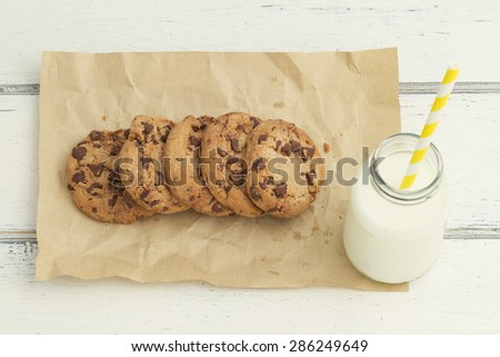 Some chocolate chip cookies and a school milk bottle - stock photo