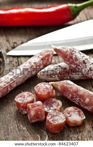 some chopped little salami on wood - stock photo