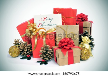 some christmas gifts wrapped with wrapping paper of different colors and ribbon bows, and some christmas ornaments, and a signboard with the sentence merry christmas written in it - stock photo