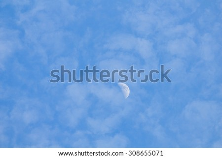 Some clouds and little half moon in the blue sky. - stock photo
