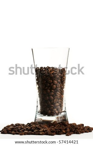 some coffee beans in a glass surrounded by coffee beans