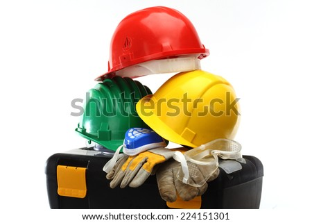 Some color protective helmets and toolbox on white  - stock photo
