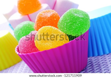 some colorful bowls with candies of different colors on a purple woven surface - stock photo