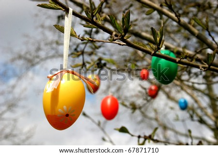 Some colourful easter eggs hanging at branches - stock photo