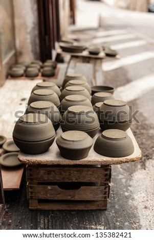 some crockery arranged on the street in a typical italian artisan shop - stock photo