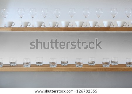 Some cups and glasses on a shelf at wall