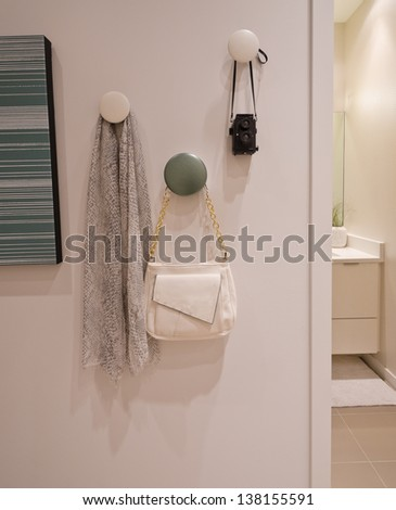 Some decorations hanging on the wall hooks. Scarf, kerchief, bag, pouch and photo camera. Interior design. Fragment. - stock photo