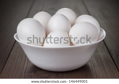 some eggs in white bowl on wooden table - stock photo