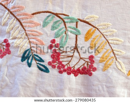 Some embroidered tree branches with leaves and red berries on the tablecloth - stock photo