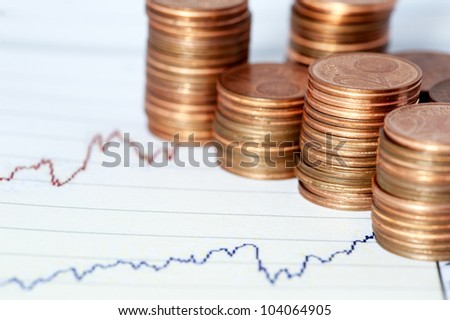 Some euro coins on a financial chart - stock photo
