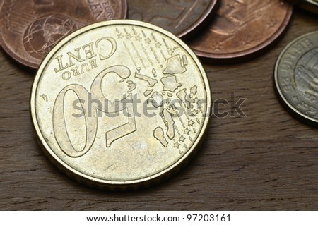 Some euro coins, on of fifty cent, on wooden table - stock photo