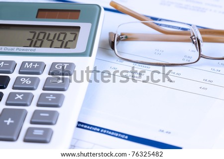 Some figures written in a paper. There is a calculator and a glasses in the scene. The photo have a deliberate blue photographic filter. - stock photo