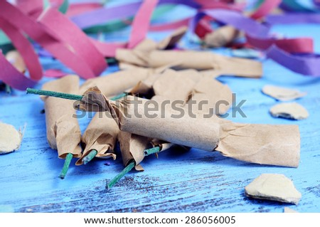 some firecrackers, and confetti and streamers of different colors on a rustic blue wooden surface - stock photo