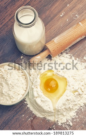 Some flour with an egg in it and a bottle of milk - stock photo