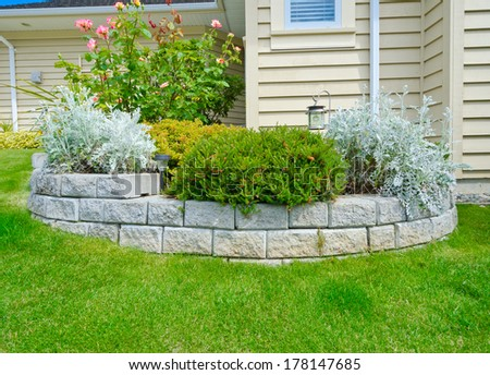 Some flowers and nicely trimmed bushes in the stoned flowerbed on the front yard in the suburbs of Vancouver, Canada. Landscape design. - stock photo