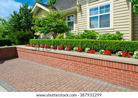 Some flowers and nicely trimmed bushes on the brick flowerbed and nicely paved yard in the suburbs of Vancouver, Canada. Landscape urban design. - stock photo